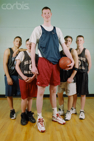 "ca. 2000, Worcester, Massachusetts, USA --- Neil Fingleton (7'6"") with his basketball team at Holy Name Central Catholic High School. He now plays center for Holy Cross College. --- Image by © Michael Brennan/CORBIS"